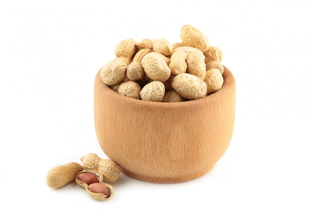 Dried peanuts in wooden bowl isolated on white background.