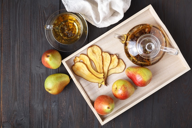 Dried pears with tea on a wooden tray