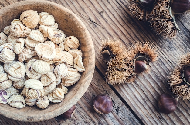 Dried peeled chestnuts on wooden background