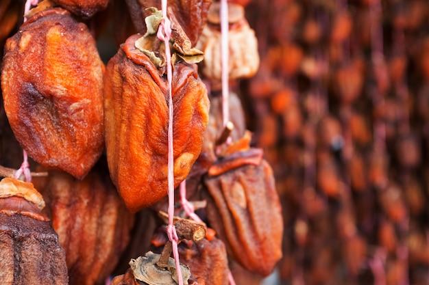 말린 감은 밧줄에 매달려 공기 건조 말린 과일입니다. 프리미엄 사진