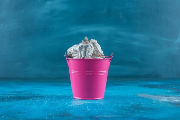 Cachi secchi in un secchio, sul tavolo blu.