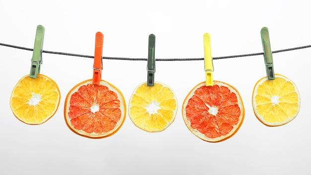 말린 감귤 조각이 빨래 집게에 매달려 있습니다. 건강과 비타민 식품