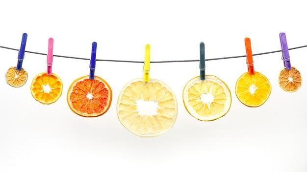 말린 감귤류 조각이 흰색 배경에 있는 빨래집게에 매달려 있습니다. 건강 및 비타민 식품