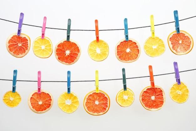柑橘系の果物の乾燥した部分が洗濯ばさみにぶら下がっています