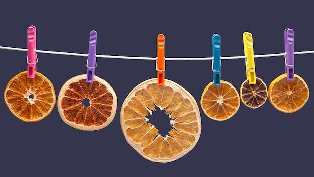 Сушеные кусочки разных цитрусовых висят на цветных прищепках на синем