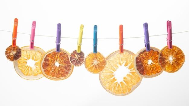 Сушеные кусочки разных цитрусовых висят на цветных прищепках.