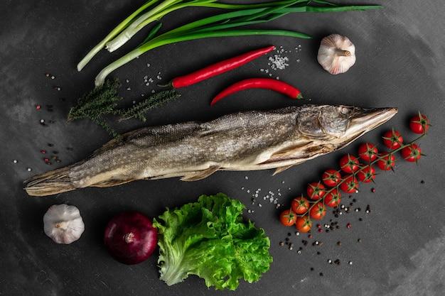 Сушеная щука с овощами на черной поверхности, вид сверху, концепция фермерского рынка