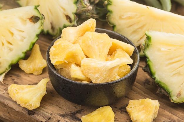 木の背景のボウルに乾燥パイナップル
