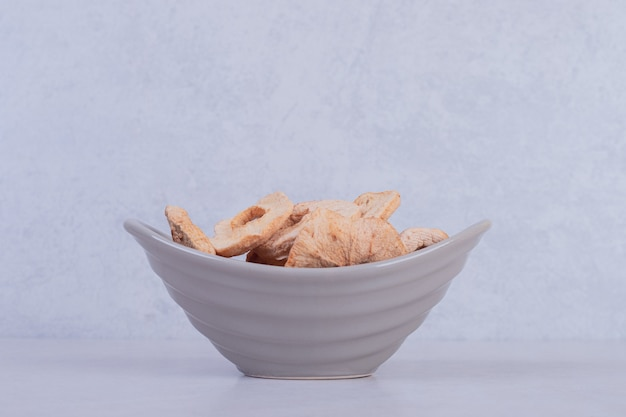 Dried pineapple rings in bowl on white surface.
