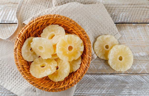 Dried pineapple rings in a wicker basket on kitchen towel