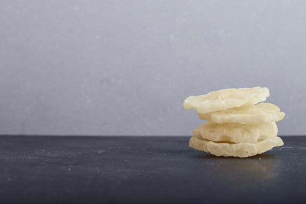 灰色の表面に乾燥したパイナップルスライス。