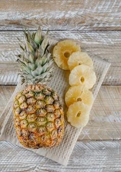 キッチンタオルの上に新鮮なパイナップルとパイナップルを乾燥