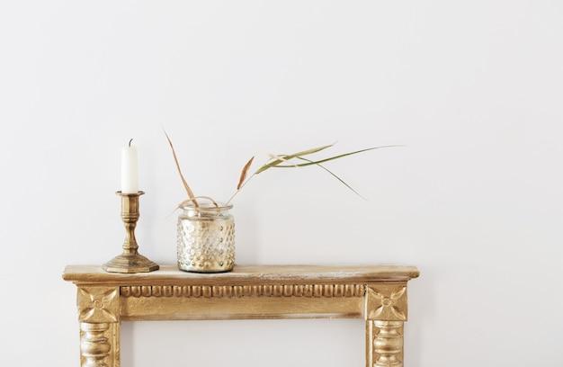 白い背景の上の古い棚の上の金色の瓶に乾燥植物