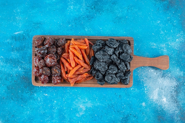 Prugne secche e albicocche su una tavola sulla superficie blu