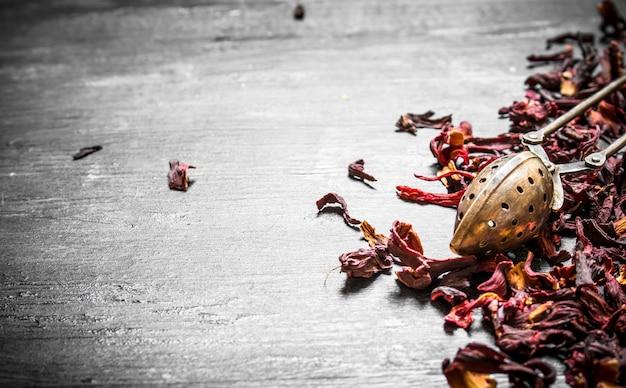 Высушенный гранатовый чай на черном деревянном столе.