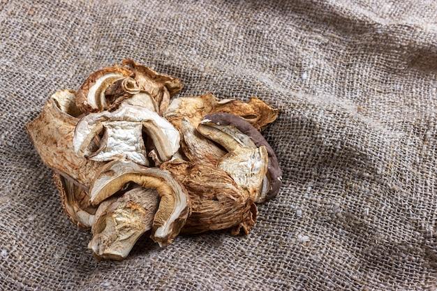 Сушеные белые грибы на мешковине. вид сверху.