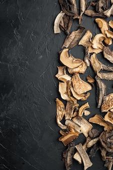 검은색 배경에 말린 포르치니 버섯 세트, 위쪽 뷰 플랫 레이, 텍스트 카피스페이스를 위한 공간