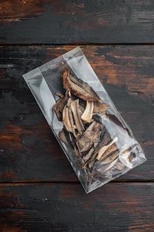 乾燥したポルチーニ茸のセット、古い暗い木製のテーブルの背景、プラスチックパック、上面図フラットレイ