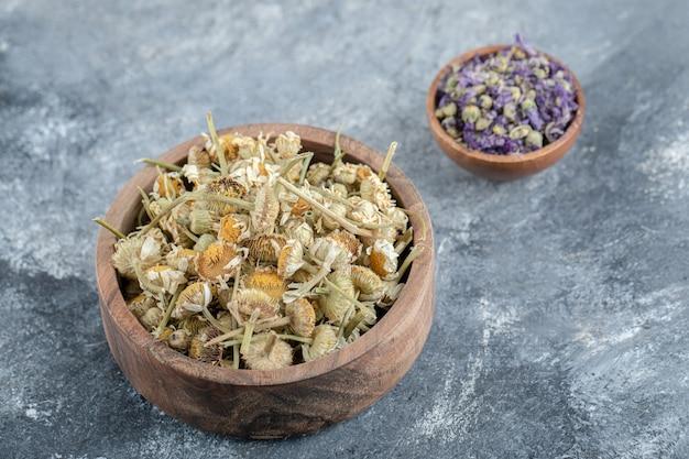 Fiori viola secchi e camomille in ciotole di legno.