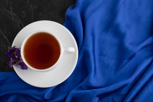 Fiori viola secchi con una tazza di tè caldo su un tavolo nero.