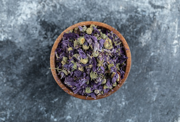 Fiori viola secchi in ciotola di legno.