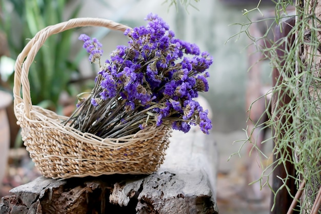 Dried purple statice flower in the basket on timber