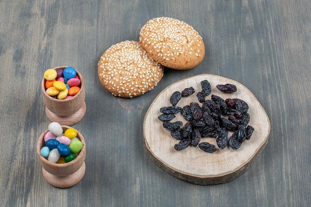 Uva passa secca con panino e caramelle colorate su un tavolo di legno