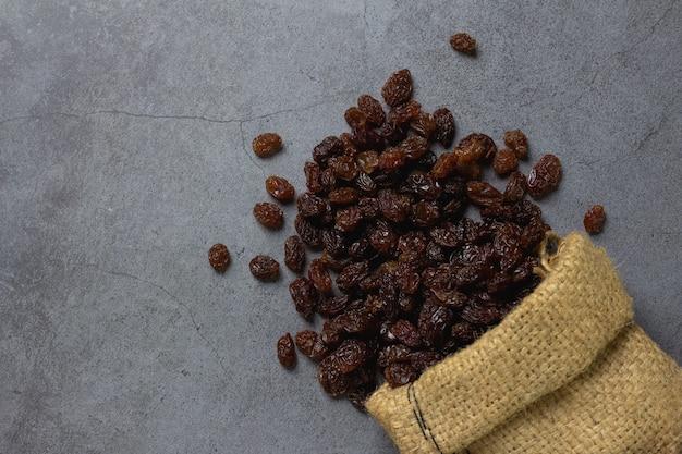Dried raisins in burlap bagl on table