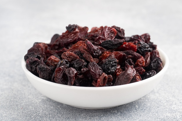 Dried raisins from dark grapes in a plate on a gray concrete background, copy space. top view