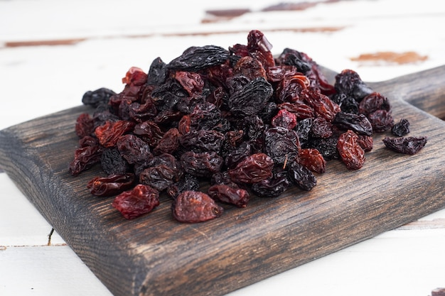 Dried raisins from dark grapes in a plate on a wooden chopping board.