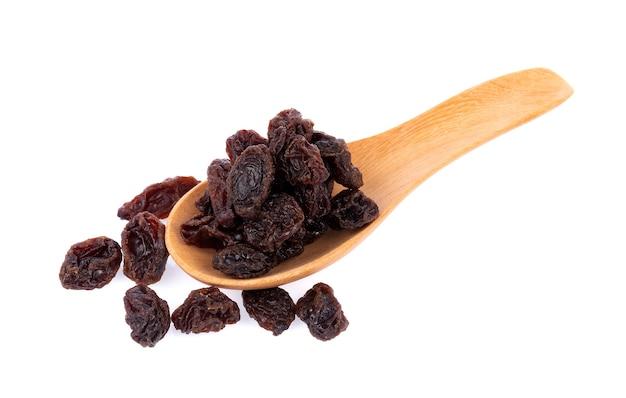 Dried raisins in spoon on white background
