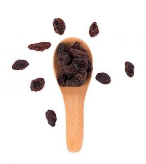 Dried raisins in spoon on white