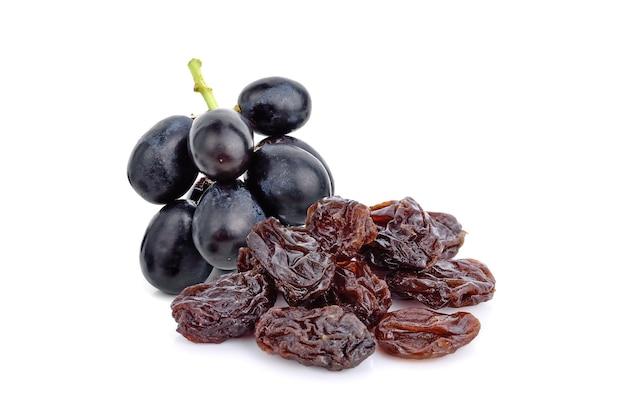 Dried raisins with fresh grape on white background