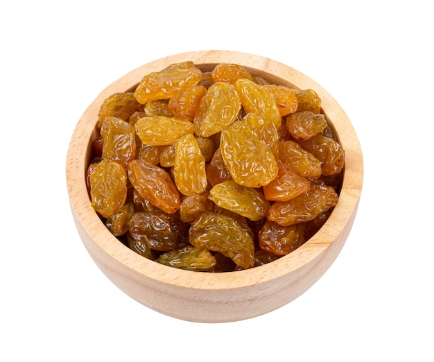 Dried raisins in wood bowl on white table.
