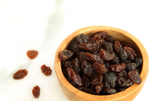 Dried raisins in wooden bowl on white marble background with copy space.