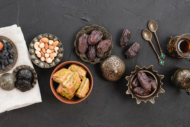 Dried raw organic dates; nuts and baklava on metallic iron plate over the black backdrop