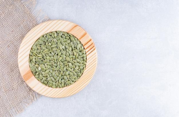 Сушеные сырые пепиты на деревянной тарелке рядом с кусками ткани на мраморной поверхности