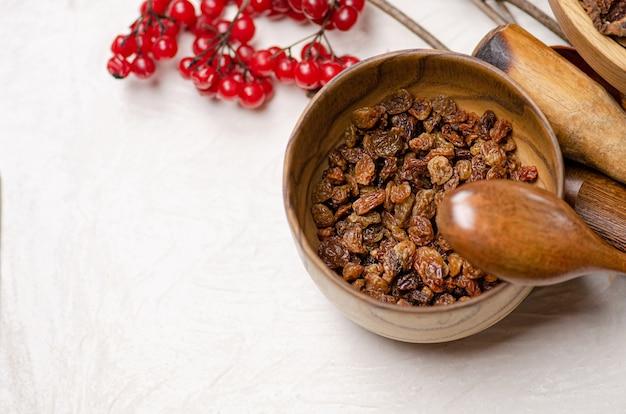 Dried raw raisins in wooden bowl. natural raisins in a bowl. bowl with dried raisins.