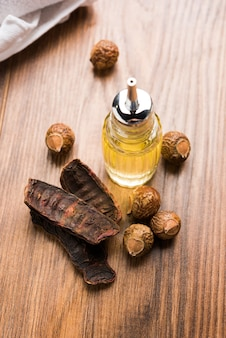 Сушеные сырые шикакай и рита или порошок мыльного ореха в миске или эфирное масло, выборочный фокус