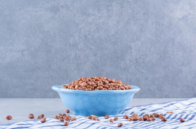 大理石の表面のタオルの上で青いボウルに山盛りにされた乾燥した小豆