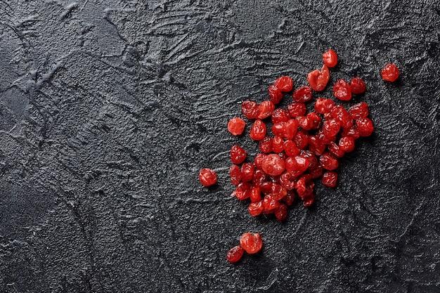 Сушеные красные вишни на черном фоне с копией пространства.