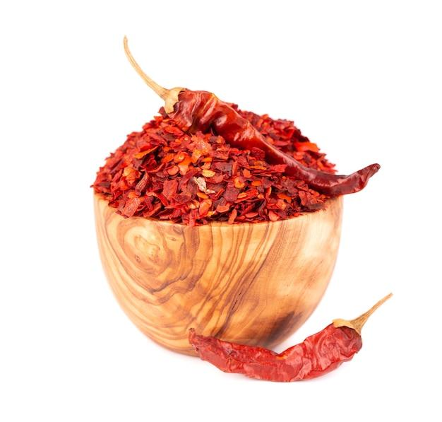 Сушеные красные хлопья чили в оливковой миске, изолированные на белом фоне, нарезанный перец чили кайенский перец