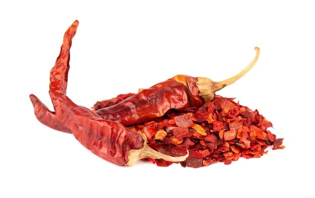 Сушеные красные хлопья чили с семенами, изолированные на белом фоне. нарезанный чили кайенский перец. специи и зелень.