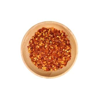 白い背景の上の木製のボウル分離で乾燥赤唐辛子フレーク
