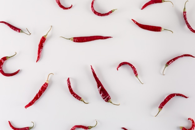 Dried red chili pepper on white surface top view