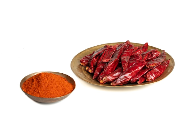 Dried red chili peppers with chili powder on white background