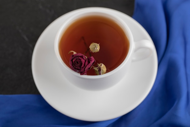 Rosa appassita in una tazza di tè caldo su un tavolo nero.