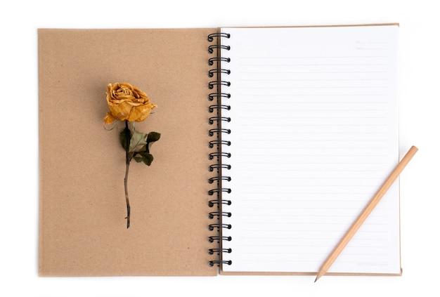 ノートパソコンに鉛筆で乾いたバラの花