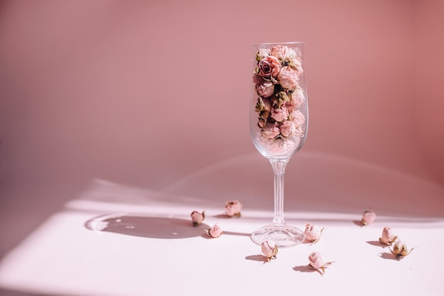 Сушеные цветы розы в бокале для вина на солнце на розовом