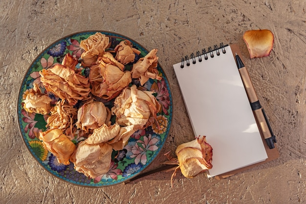 Dried rose flowers on old vintage plate in sunlight. dry roses heads on lit by the sun and a notepad with pan for scrapbook. copy space.